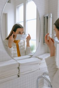 Image of a woman looking in a mirror for the waxing co
