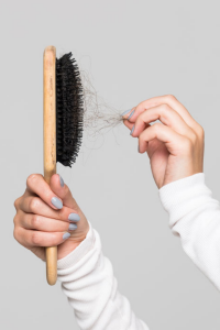 woman hands pulling hair from comb image for the waxing co