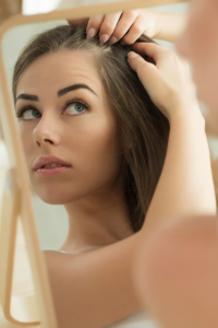 woman looking on her hair in front of mirror image for the waxing co